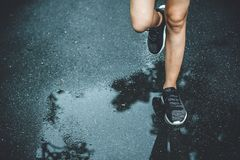 Urban city running jogging sport healthy people concept close up legs and shoes run. On wet asphalt road royalty free stock photo