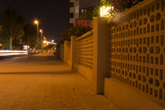 Urban City Street with Car Light Trails And Decorated Fence at N Stock Images