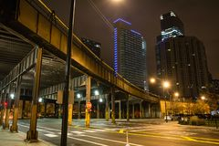 Urban city street corner with vintage train bridge. And skyscrapers in Chicago at night stock photo