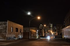Urban city street with vintage industrial warehouses. And the Chicago skyline with the moon at night Royalty Free Stock Photos