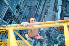Urban climbing: rock climber hanging on jib of construction cran Royalty Free Stock Photo