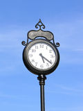 Urban clock. Old classic urban clock on the post isolated on the blue sky Royalty Free Stock Images