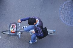Urban communication. Japanese teen throwing a quick look to the mobile phone screen on a bicycle while is waiting to the traffic light Stock Photography