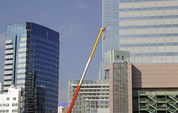 Urban construction abstract. Image of the upper part of a crane between the skyscrapers in a big city Stock Photo