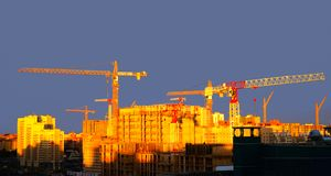 Urban construction cranes in sunlight. Boom construction cranes against the sky royalty free stock image