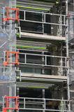 Urban construction site scaffolding to support work crew Stock Images