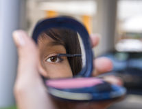 Urban cosmetics. Mirror image of a woman's eye while she is applying mascara against a urban blurred background Royalty Free Stock Images