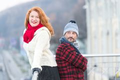 Urban couple on the bridge. Happy couple standing back to back. Man and woman look in one way. Smiling red hair lady and happy man stock image
