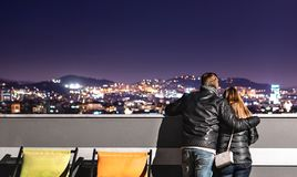 Urban couple looking at the city view from rooftop. Boyfriend holding arm around his girlfriend. Romantic evening for date. stock image