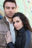 Urban couple standing by wall Stock Photography