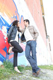 Urban couple standing by wall Royalty Free Stock Photo