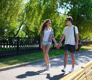 Urban couple teen in love walking. In the summer park royalty free stock photo