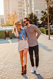 Urban couple walking on the street and smiling Stock Images