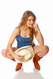 Urban cowgirl. Nineteen year old young woman looking into camera with hat in provacative placement Royalty Free Stock Photos