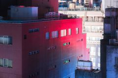 Urban creepy building and red and blue reflection. Night cityscape from the roof top in Tokyo, view of an old 80`s building lightened with a blue and red Royalty Free Stock Photo