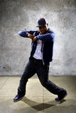 Urban Dancer on a Concrete Background. Young black male dancing hip hop style in an urban setting.  He is wearing a hoodie on a concrete background Royalty Free Stock Photos