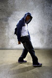 Urban Dancer on a Concrete Background. Young black male dancing hip hop style in an urban setting.  He is wearing a hoodie on a concrete background Stock Images