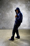 Urban Dancer on a Concrete Background. Young black male dancing hip hop style in an urban setting.  He is wearing a hoodie on a concrete background Royalty Free Stock Photography