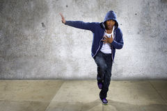 Urban Dancer on a Concrete Background. Young black male dancing hip hop style in an urban setting.  He is wearing a hoodie on a concrete background Stock Photos
