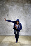 Urban Dancer on a Concrete Background. Young black male dancing hip hop style in an urban setting.  He is wearing a hoodie on a concrete background Stock Photography
