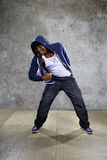 Urban Dancer on a Concrete Background. Young black male dancing hip hop style in an urban setting.  He is wearing a hoodie on a concrete background Stock Image