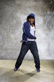 Urban Dancer on a Concrete Background. Young black male dancing hip hop style in an urban setting.  He is wearing a hoodie on a concrete background Royalty Free Stock Photo