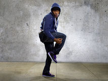 Urban Dancer on a Concrete Background. Young black male dancing hip hop style in an urban setting.  He is wearing a hoodie on a concrete background Royalty Free Stock Image