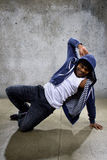 Urban Dancer on a Concrete Background. Young black male dancing hip hop style in an urban setting.  He is wearing a hoodie on a concrete background Royalty Free Stock Images