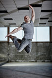 Urban dancer jumping. Urban dancer in an industrial setting executing a jump over a grunge background Royalty Free Stock Photo