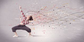 Urban dancing with lines and splatter. A young contemporary energetic dancer in action in front of a grey wall background with lines, spray dots and splatter Royalty Free Stock Images