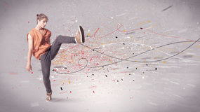 Urban dancing with lines and splatter. A young contemporary energetic dancer in action in front of a grey wall background with lines, spray dots and splatter stock image