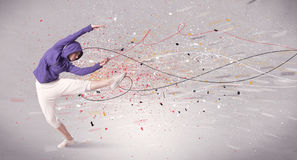 Urban dancing with lines and splatter. A young contemporary energetic dancer in action in front of a grey wall background with lines, spray dots and splatter Stock Photo