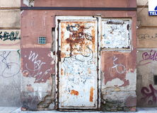 Urban decay. Wall with peeling paint, graffiti, and rusty metallic door Royalty Free Stock Images
