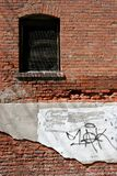 Urban decay. An old brick wall along an alley, crumbling and defaced stock photography