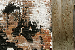 Urban Decay. Detail of old, abandoned brick factory wall with chipped and peeling paint. Copy space on boarded up door stock photos