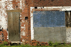 Urban Decay. Detail of old, abandoned brick factory wall with chipped and peeling paint. Copy space on boarded up door or blue and grey boarded up window stock photo