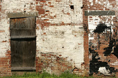 Urban Decay. Detail of old, abandoned brick factory wall with chipped and peeling paint and boarded up door royalty free stock photography