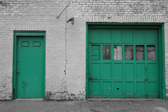 Urban Decay Garage Doors. Green commercial garage doors with broken square window panes and white brick wall with peeling paint Royalty Free Stock Photos