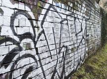Urban decay graffiti on wall. Wall Graffiti urban decay on canal Royalty Free Stock Photography