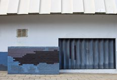 Urban decay with wall design and rustic door. And corrugated roof Royalty Free Stock Image