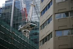 Urban development. Crane on top of building in dense urban environment Royalty Free Stock Photo