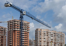 Urban development. Blue tower crane on a background of new buildings Stock Photo