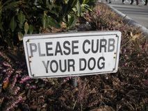 Urban Dog Obedience, Please Curb Your Dog Sign royalty free stock image