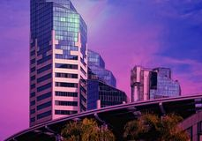Urban Downtown Skyline Modern Buildings in a Purple Haze. Beautiful new tall vertical modern downtown buildings in a colorful brilliant purple sky haze royalty free stock photo