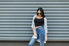 Urban elegant young hipster woman in trendy black sunglasses with long hair in a black vintage t-shirt in a summer jacket stock photos