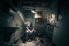 Urban explorer in an abandoned room. Man in a respirator exploring an abandoned room Royalty Free Stock Photography