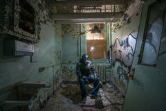 Urban explorer in an abandoned room. Man in a respirator exploring an abandoned room Royalty Free Stock Photos