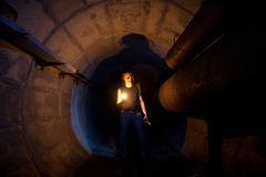 Urban explorer with candle in underground communication, heating main, sewer tunnel, etc. Urban explorer with candle in underground communication, heating main stock photography