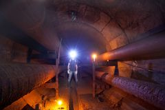 Urban explorer with candle in underground communication, heating main, sewer tunnel, etc. Urban explorer with candle in underground communication, heating main stock photo
