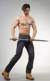 Urban Fantasy. Male model posing in a contemporary outfit with a sword stock photo